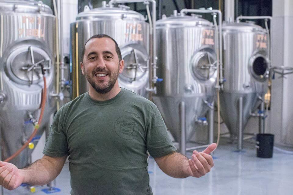 man in front of brewer equipment
