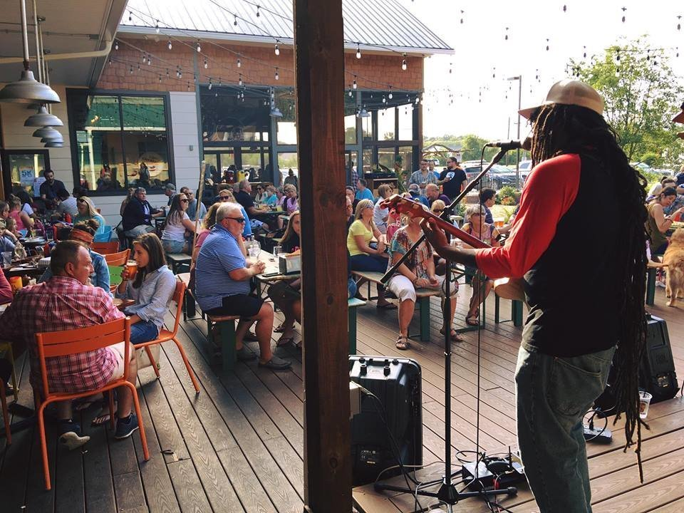 Musician on outdoor stage playing guitar to large crowd seating and dining