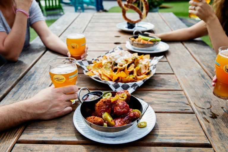 Group of friends at table in The Backyard enjoying starters withcraft beers in glasses