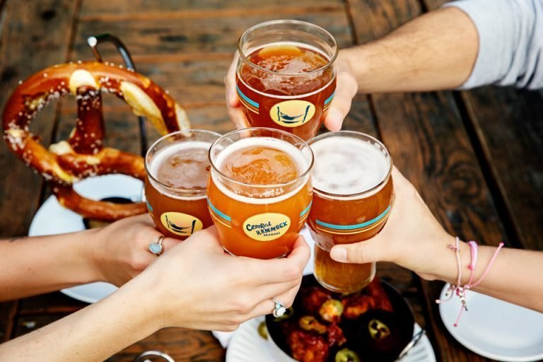 4 hands toasting craft beers over preztel and appetizers on table