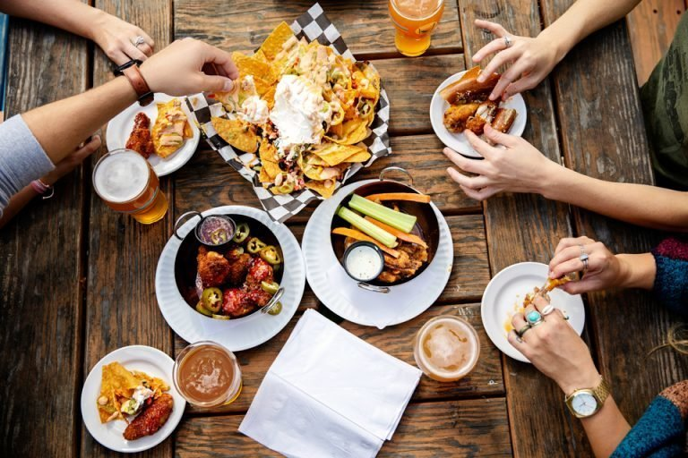 Overhead view of table hands reaching for wings, nachos and beers