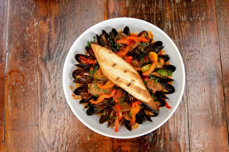 Overhead view of mussels, veggies, and roll in dish on table