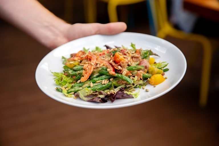 Server's hand holding plate of salad