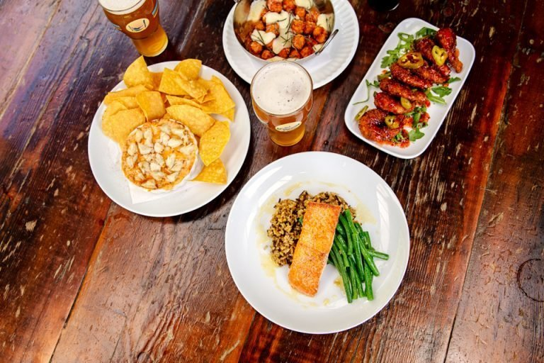 overhead view of starter, main item, wings and craft beers