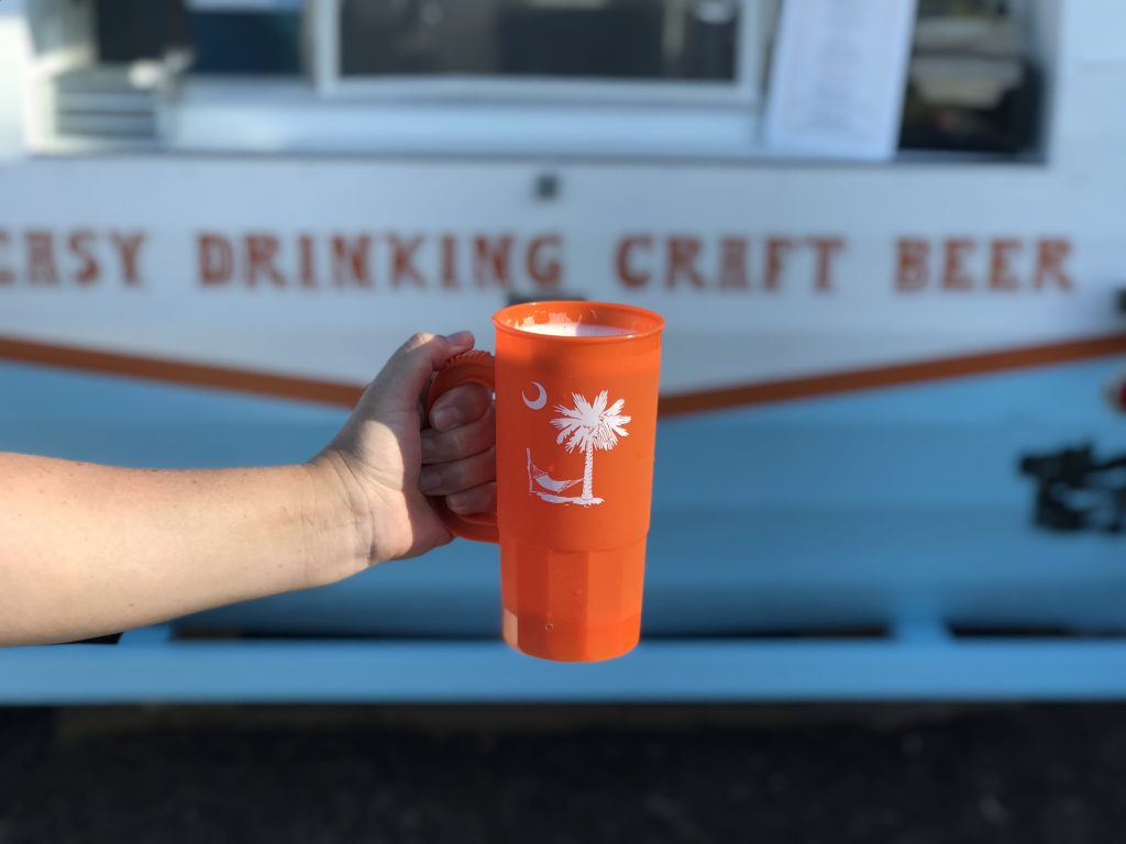 hand holding craft beer in plastic souvenir cup with Crooked Hammock logo in front of camper bar