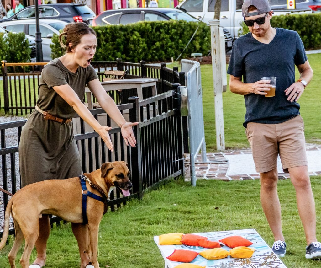 Young couple with dog playing lively game of cornhole in Hammock backyard