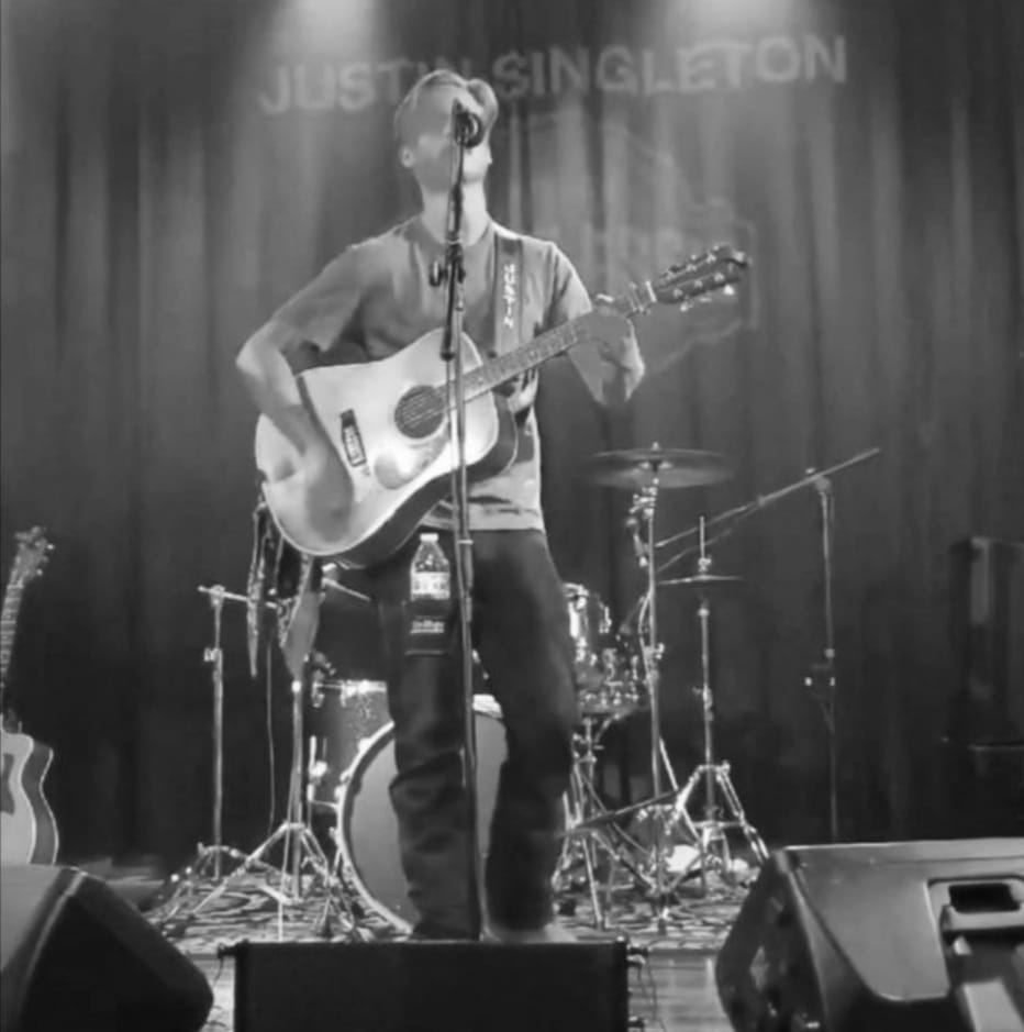 Justin Singleton playing acoustic guitar on stage in front of drumset