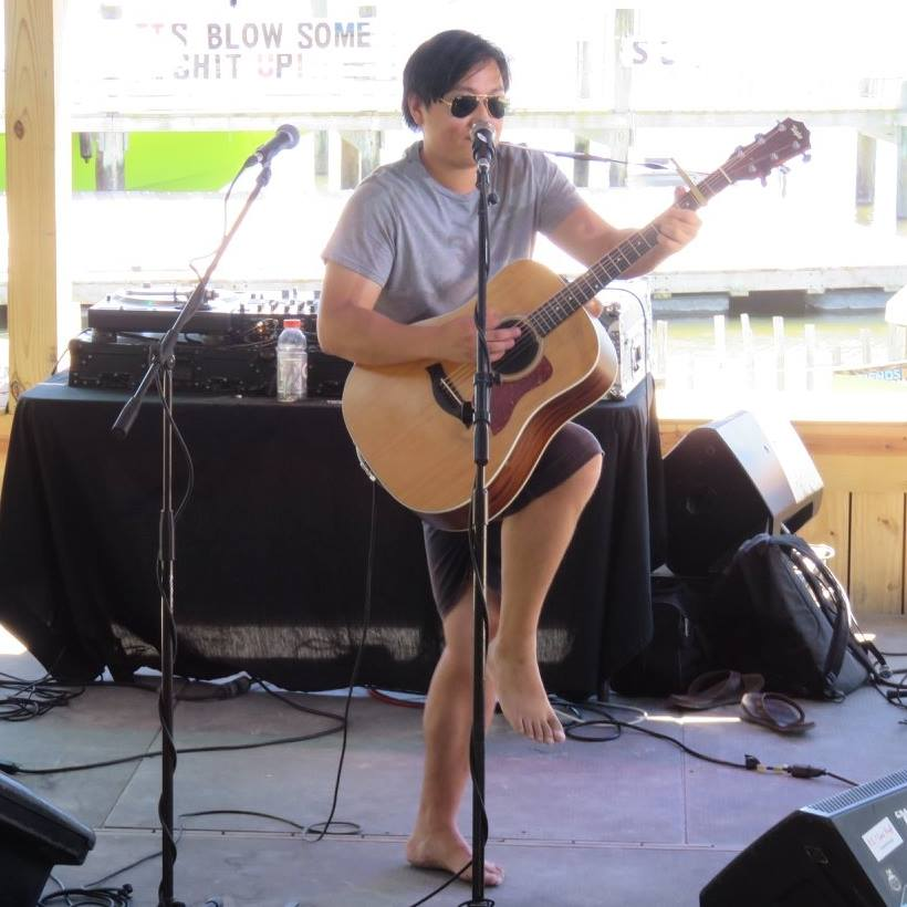 Sam Capolongo playing guitar barefoot on stage